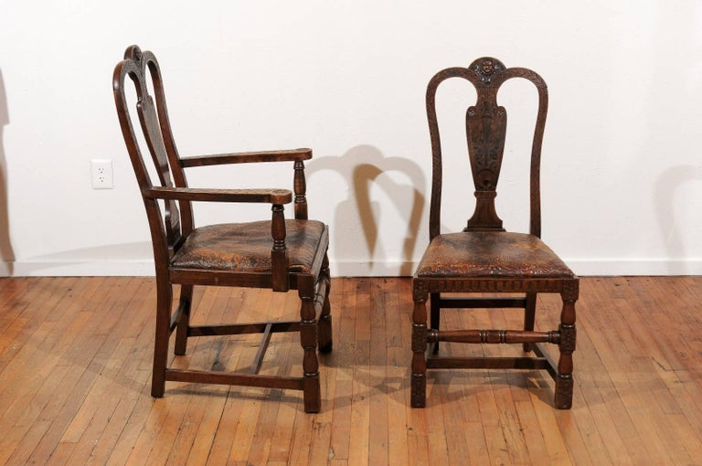 19th Century set of eight English dining chairs having two armchairs and six side chairs.  The chairs are made of solid oak with acanthus carved side and top rails surrounding a marquetry inlaid backsplat and crowned by a carved cherub.  The chairs