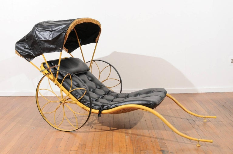 Mid-Century rickshaw by Russell Woodard in the original yellow finish with a removable and collapsible black vinyl cover with gold fringe. The rickshaw has its original removable black vinyl seat cushion tufted with brass buttons on the front and