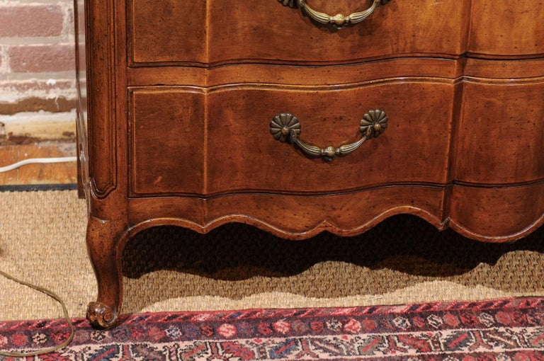 Mid-20th century Louis XV style three drawer commode of walnut with a scalloped front, brass bail hardware, and a fitted top dresser drawer.