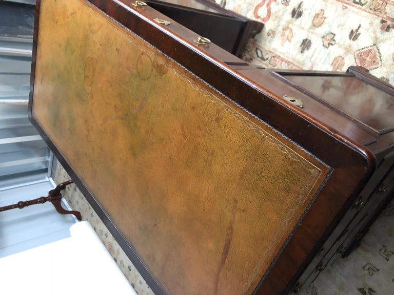 19th century English kneehole desk of mahogany created in the Regency style. The writing surface has an inset camel leather embossed top. The front of the case contains three drawers over a kneehole opening and cabinet door, flanked by paneled
