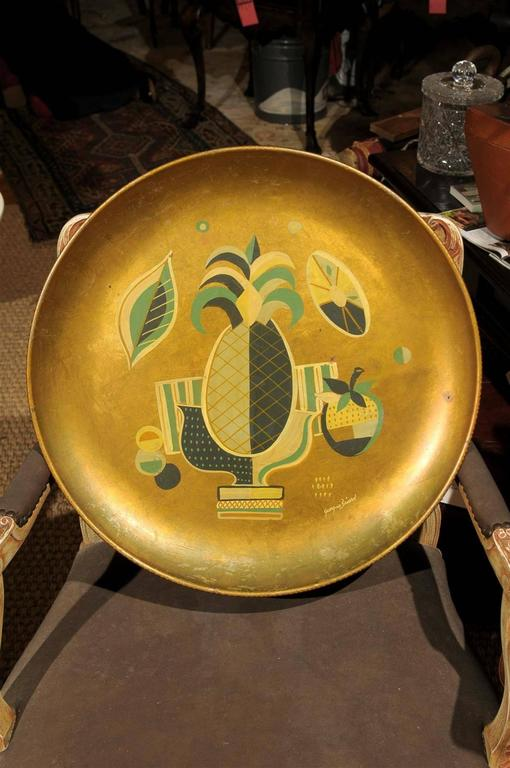 Mid 20th Century large gold tole serving tray or wall plaque by American accessory designer Georges Briard and of the Hollywood Regency period.  The hand painted design centers around a pineapple and is signed in the lower right corner.  There is a