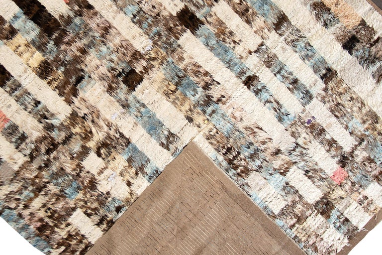 A modern 21st century Moroccan style rug with an all over ivory motif. This rug measures at 10'9