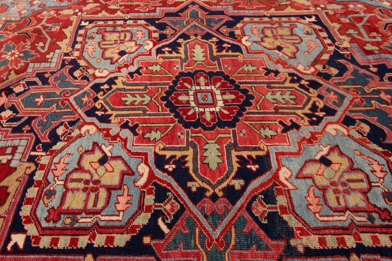Measures: 8.10x12. Has a rust field and a traditional medallion design in blue tones, and was hand-knotted in 1925.   The city of Heriz is situated in the northwest of Iran, not far from the greater city of Tabriz. In the city and its surroundings