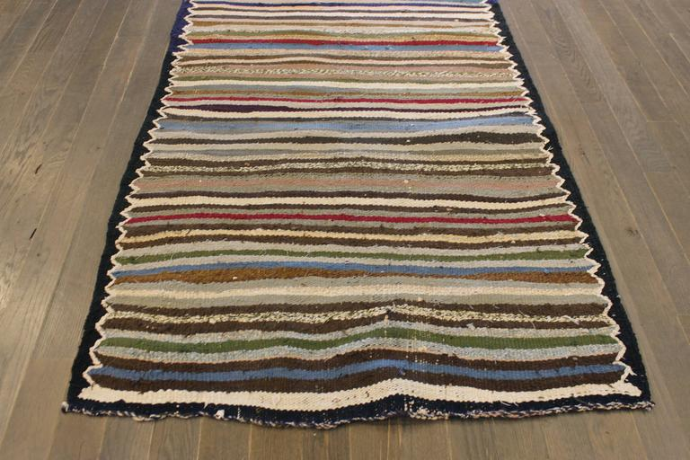 A hand-knotted Kilim rug with a striped design on a black field. Accents of ivory, green, red and blue throughout the piece. This rug measures 3'.5 x 9'.4.