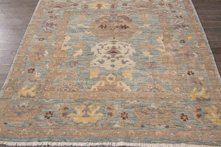 A hand-knotted Sultanabad rug with a floral design and border. Accents of blue, brown and beige throughout.