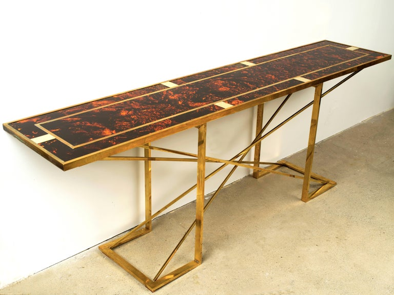 Stunning and dramatic is this large faux tortoise and brass console table attributed to Romeo Rega. The combination of the bright faux tortoise resin with the geometric lines of the brass creates a unique table to say the least. Found in Italy this