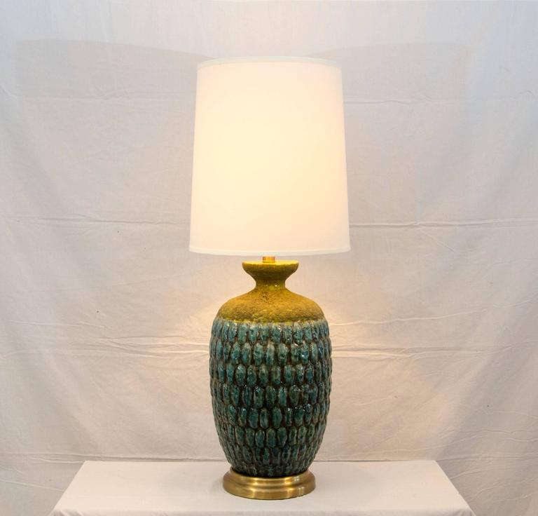 Larger size Studio Pottery table lamp with a new shade. The predominant color is a sea-foam blue with underlying accents of chartreuse. Towards the top part of the base it has a grayish lava style glaze also with underlying chartreuse accents. The