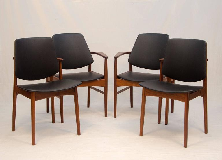 Unusual set of chairs designed by Arne Hovmand-Olsen. Two armchairs and two side chairs. The two armchairs are designed so that the arms wraparound the backs in a continuous form. There are brass stand-offs between the backs and the back legs.