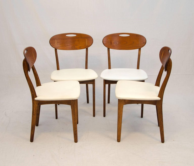 Comfortable and unusual design with a combination of wood types with teak backs, Hans Wegner style oak inserts, and oak chair frames. Retains designer and manufacturer's markings. These chairs are especially easy to move by using the cut-out handle