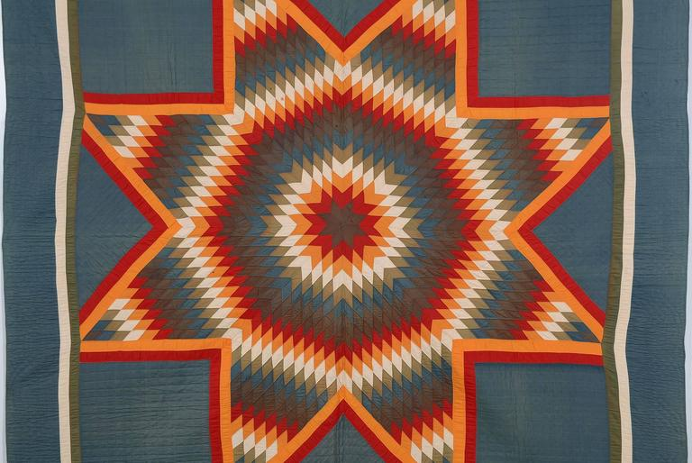 Red and orange used for the center and outlines of this Lone Star quilt make it look as though it's on fire. The colors contrast very effectively with the gray/green background. The background color has softened from its original but it has done so