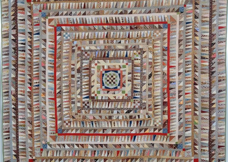 This pieced center Medallion quilt is an extraordinary sampler of fabrics and design. Each frame is filled with a huge selection of fabrics, most of which are printed. A variety of triangle shapes makes for variation but with consistency. The center