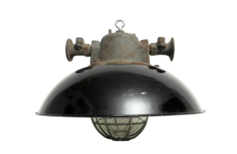Ceiling lamps with cast iron top, dome-shaped shade, and caged thick glass.
