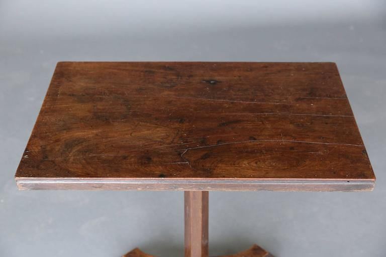 19th century narrow mahogany table with interesting base on 4 feet.