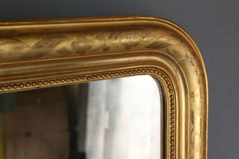 19th century Louis Philippe gilt mirror with pearl detail along the inside perimeter. Gilt is etched with a floral design that meanders along the perimeter. Original mercury glass.