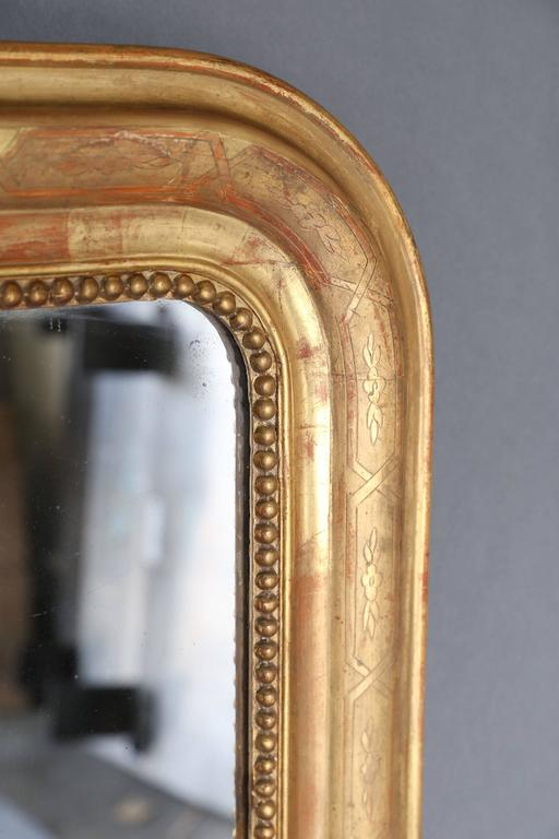 19th century Louis Philippe gilt mirror with pearl detail on the interior perimeter. Etching on gilt is an intertwining design with simple floral motifs throughout. Mercury glass is original.