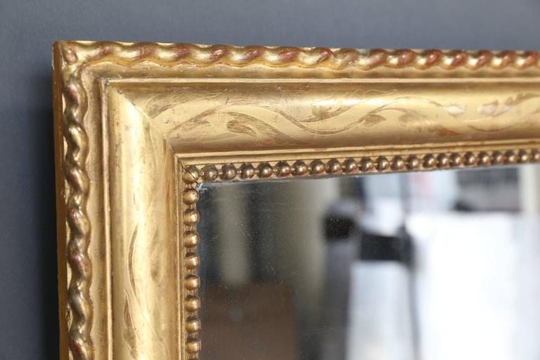 Large rectangular overmantel gilt mirror with etching and rope detail around etched perimeter. In the interior perimeter there is the pearl detail frequently seen in French mirrors of this period. Original mercury glass, circa 1870.
