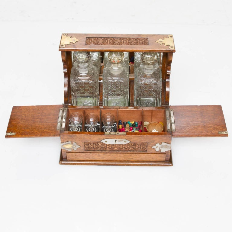A very nice quality English oak carved decanter set and case fitted interior with a release button revealing a card drawer. Very well carved and handsome brass mounts.