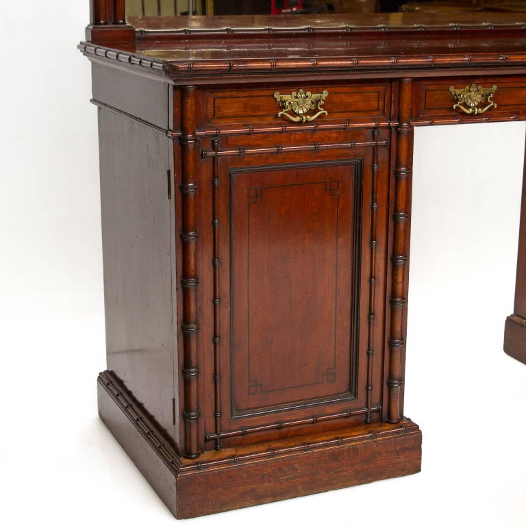 A fine English pedestal sideboard with mirror back and bamboo moldings. The sideboard is made of mahogany wood. With ebony string inlays. The mahogany is figured on the top serving area and a ribbon and straight cut to the fronts and sides. Brass
