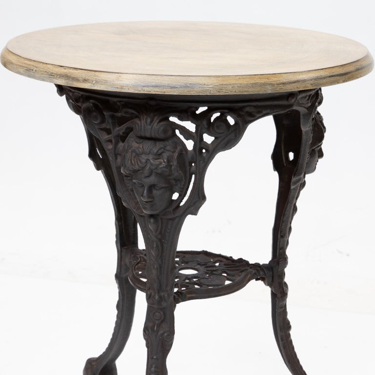 English pub or bistro table with a black iron base and a painted top.