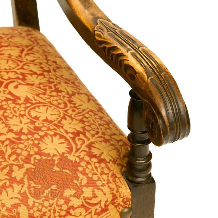19th century Louis XIII style walnut armchair with carved call feet and carved front stretcher. This chair was recovered with a nice fabric. Wonderful patina and color to the wood. Very sturdy.