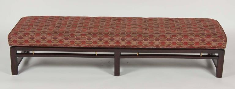 An Edward Wormley for Dunbar upholstered six leg mahogany bench with brass detail.