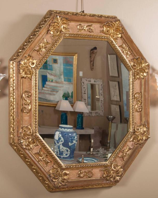 A handsome very early 18th century Italian carved and giltwood octagonal mirror.