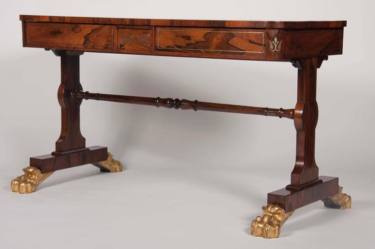 An English Regency, brass inlaid, rosewood library table with gilt paw feet.