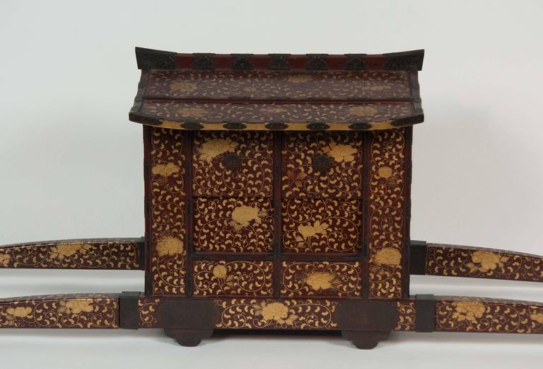 A Japanese Edo-Meiji period Palanquin chair for the childrens festival. The form with sliding and hinged doors, decorated in gold hiramaki-e with peonies and scrolling foliage on a dark reddish-brown.