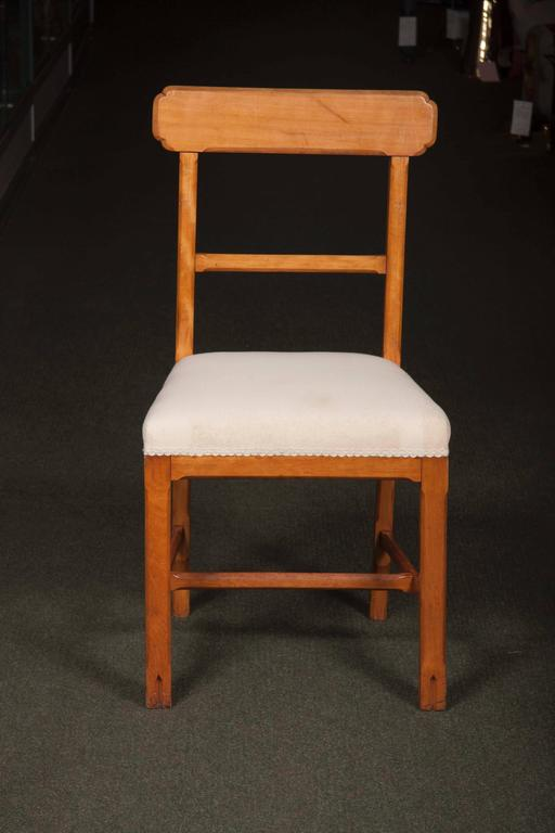 A matched set of ten Arts & Crafts dining chairs, seven of oak and three of fruitwood. Measure: Seat height 18