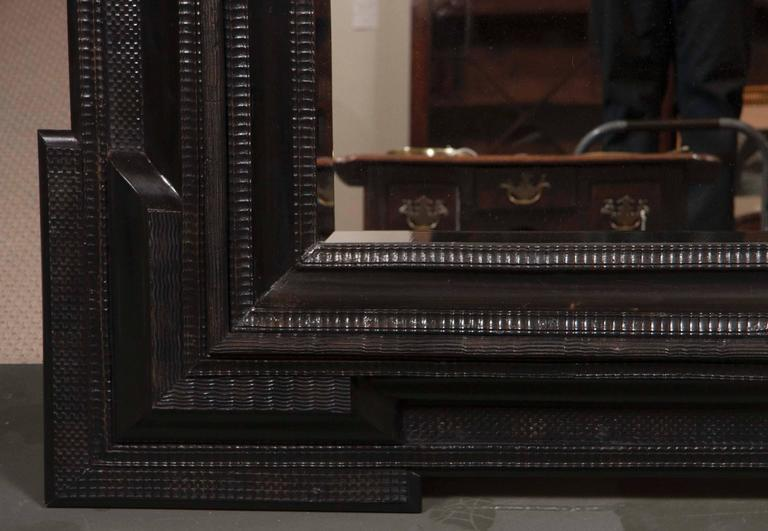 A Monumental 19th century Dutch ebonized black crossetted corner framed mirror with new beveled glass plate.