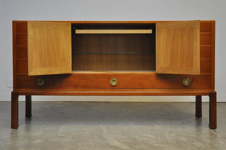 Beautiful sideboard designed by Edward Wormley for Dunbar in 1945, model 4579. The center compartment features an adjustable glass shelf and a removable glass-bottom tray.