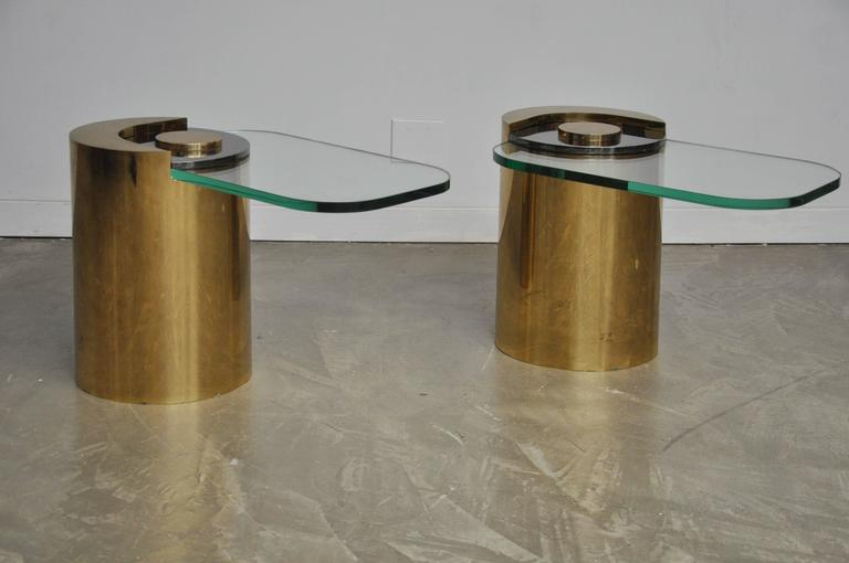 Pair of sculpture leg tables by Karl Springer. Brass bases with gun metal finish accent pieces holding cantilever glass in place. New glass, free of scratches.