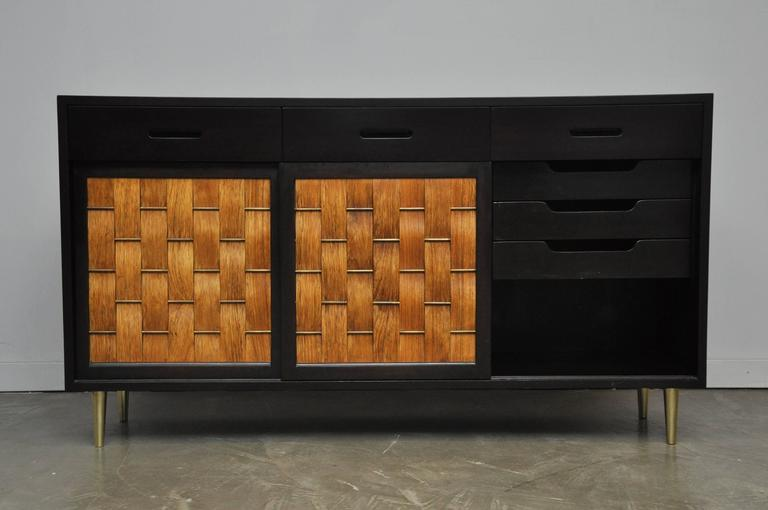Three-door credenza designed by Edward Wormley for Dunbar. Model #5668. Espresso tone mahogany case with brass details on doors and legs. Three woven bleached rosewood sliding doors. Beautiful restored condition.