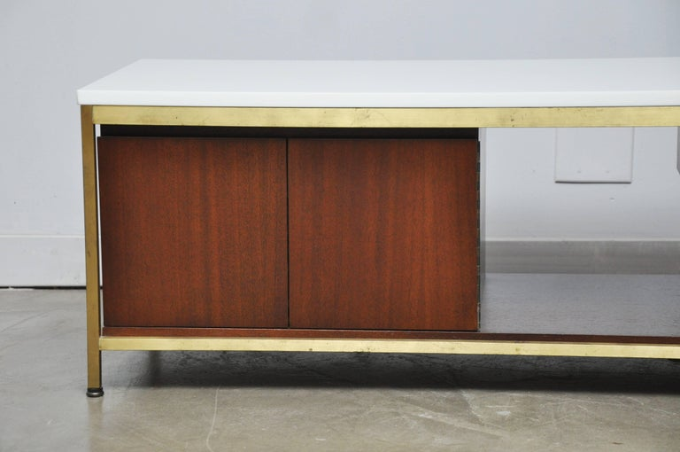 Paul McCobb coffee table or media console for Calvin Furniture. White vitrolite glass top on brass frame. This rare piece is perfect for use as an entertainment centre for flat screen tv, or as coffee table.