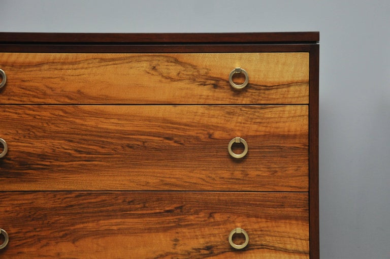 Pair of three-drawer chests by Edward Wormley for Dunbar. Model 6422. Fully restored and refinished. Dark walnut cases surround natural walnut drawer fronts with brass ring pulls.