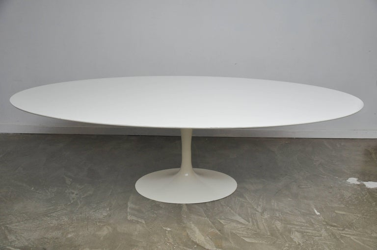 Early oval tulip dining table with cast iron base by Eero Saarinen for Knoll. This is the large 97