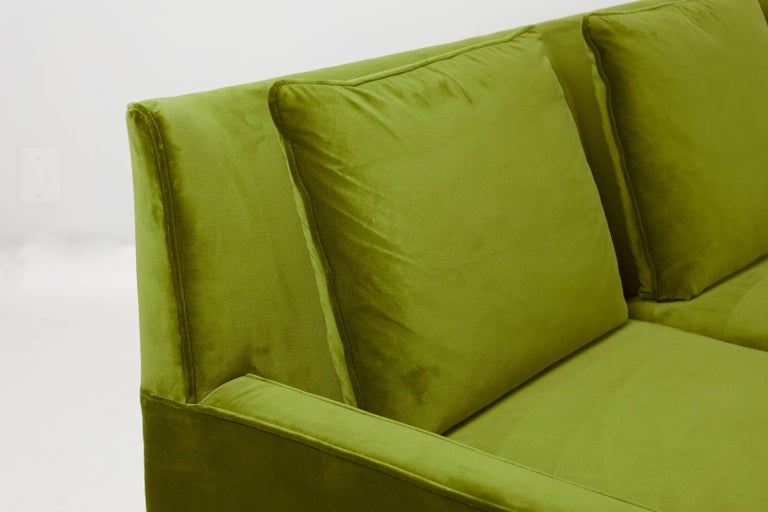 Paul McCobb wingback sofa, model 1307 for Directional furniture Fully restored walnut frame, finished in a dark walnut tone. Reupholstered in plush green velvet upholstery, with new down and foam.   We have a pair of these sofas available. Priced