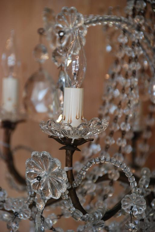 Beautiful 19th century Italian gilded wood and crystal ten-light chandelier. Lovely beaded and crystal drop-leaf ornamentation over bronze arms. Newly restored and wired.
