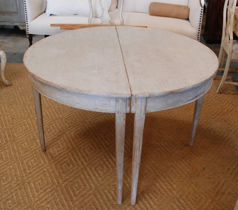 """Lovely early 19th century Swedish dining table with carved dental apron. Terrific design with detachable leaf that can be removed to form a 43"""" round table or two separate demilune tables. Swedish cream white color."""