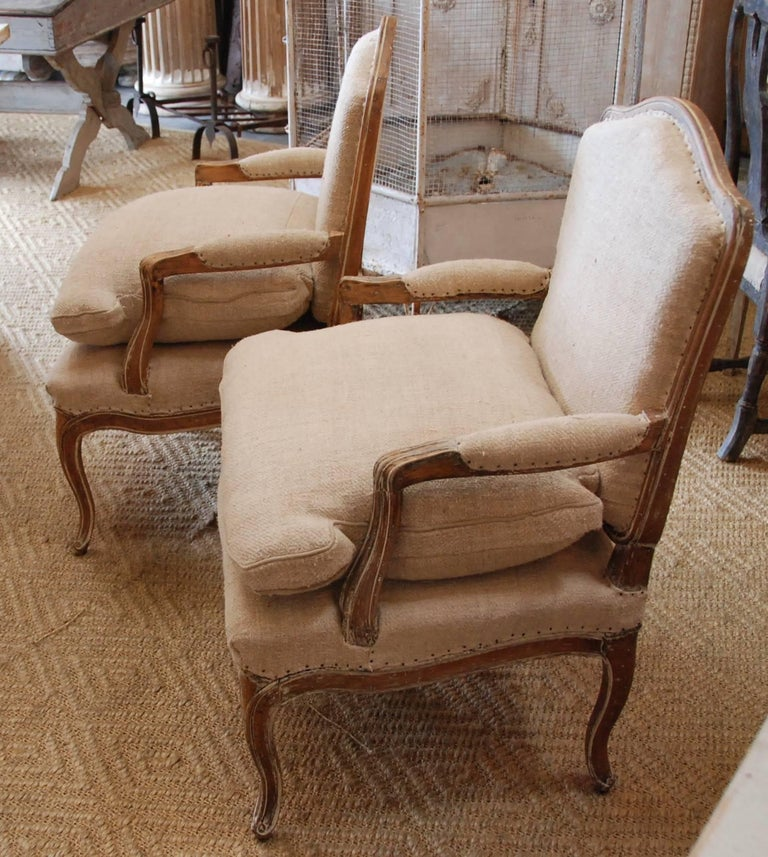 A pair of 19th century French bergère chairs stripped down to lovely aged pine patina. Upholstered in French antique hemp. Sturdy and comfortable.
