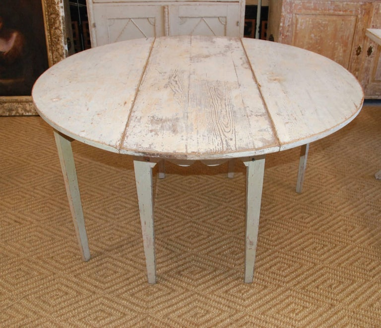 Early 19th century, Swedish drop-leaf table with original worn paint patina. The top is a lovely aged pine and the base is a pale Swedish green/blue. Closed the table measures 18