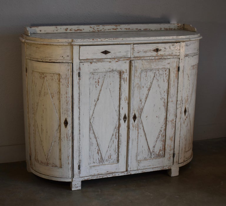 Early 19th century Swedish Gustavian demilune painted four door cupboard. All original with lovely diamond carved paneled doors and three quarter gallery top. Hinges and locks all handmade.