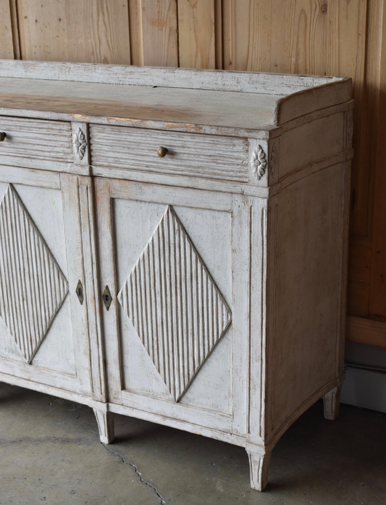 Early 19th century Swedish Gustavian style painted three door sideboard. Beautiful curved sides with wonderful three hand-carved drawers over three reeded front paneled doors. Each door is adorned with a diamond pattern. The top is surrounded with a