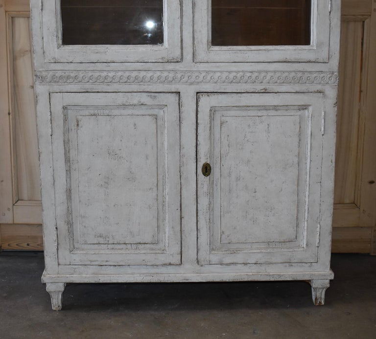 19th century Swedish glass front library cupboard with original glass and carved detail. In the Interior are 2 shelves for storage. Lovely Swedish grey/white color.
