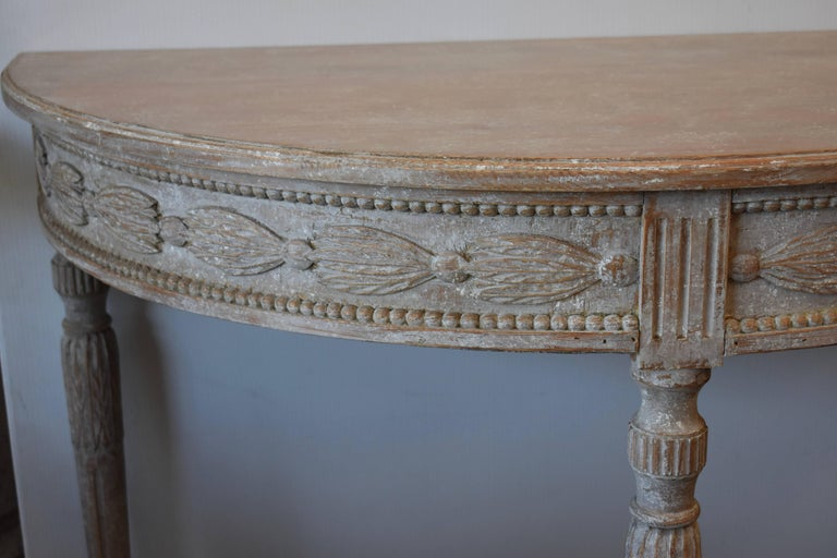 Elegant pair of demilune console tables with beautifully carved apron over lovely tapered fluted legs. Very Pretty. Stockholm, Sweden.