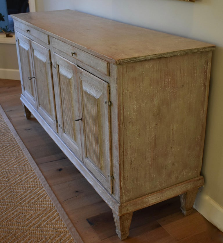 Beautiful 19th century Swedish sideboard or server with reeded paneled doors and tapered legs. Cutlery drawers and cupboards with shelves for great storage. Lovely Swedish white/grey color.