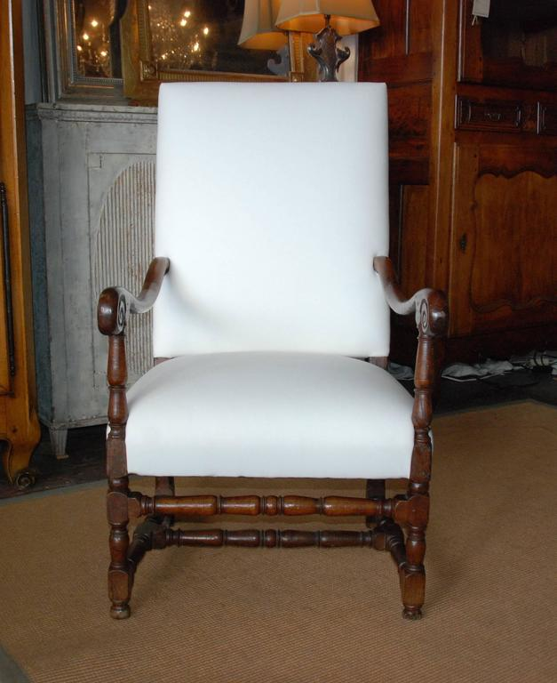 18th century French high back fauteuil with carved walnut arms and stretchers. Lovely aged patina. Newly upholstered.