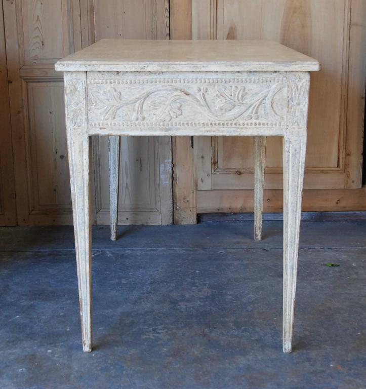 19th century Swedish console table with lovely carved apron and tapered fluted legs. The beautiful carving extends all around the table in a soft Swedish cream or white color.