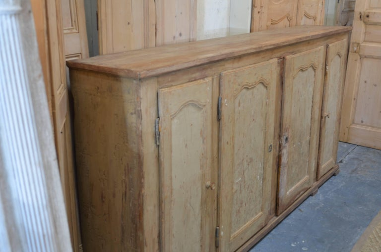19th century French painted four-door enfilade. Great ochre colored worn patina. Wonderful narrow size with lots of useful storage. Provence, France.