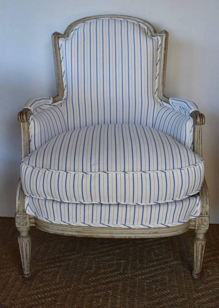 Beautiful 19th century painted French Bergere newly upholstered in blue and white stripe. Lovely carved arms and tapered legs. Great aged patina. Very comfortable with down filled cushion.